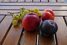 Fruits on a table. Nectarines and grapes on a wooden table stock photos