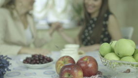 Fruits on the table and two chatting women on the background. Two smiling young women having tea at dining table.  Two Caucasian friends chatting and drinking stock video