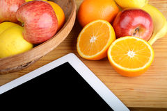 Fruits and a Tablet PC on wooden table. stock images