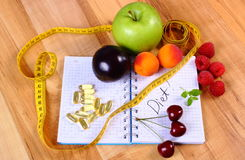 Fruits, tablets supplements and centimeter with notebook, slimming and healthy food Royalty Free Stock Photos