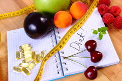 Fruits, tablets supplements and centimeter with notebook, slimming and healthy food Royalty Free Stock Photo