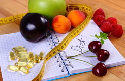 Fruits, tablets supplements and centimeter with notebook, slimming and healthy food Royalty Free Stock Photography