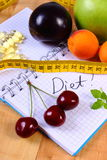 Fruits, tablets supplements and centimeter with notebook, slimming and healthy food Royalty Free Stock Image