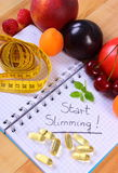 Fruits, tablets supplements and centimeter with notebook, slimming and healthy food Stock Images