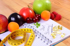 Fruits, tablets supplements and centimeter with notebook, slimming and healthy food Royalty Free Stock Images