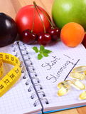 Fruits, tablets supplements and centimeter with notebook, slimming and healthy food Stock Photos