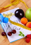 Fruits, tablets supplements and centimeter with notebook, slimming and healthy food. Fruits with mineral water, tape measure and tablets supplements on notebook Royalty Free Stock Images