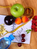 Fruits, tablets supplements and centimeter with notebook, slimming and healthy food Stock Photo