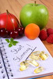 Fruits and tablets supplements with notebook, slimming and healthy food Royalty Free Stock Images