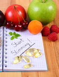 Fruits and tablets supplements with notebook, slimming and healthy food Stock Photography
