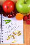 Fruits and tablets supplements with notebook, slimming and healthy food Stock Image