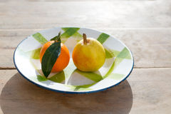 Fruits tangerine and pear in vintage porcelain dish plate Stock Images