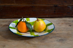 Fruits tangerine and pear in vintage porcelain dish plate retro Stock Images