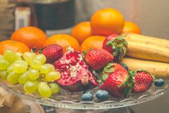 Fruits, tangerines, bananas, strawberries in a plate. Restaurant, menu concept. Background royalty free stock images