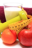 Fruits, tape, milk, green dumbbells and purple towel on white Royalty Free Stock Images