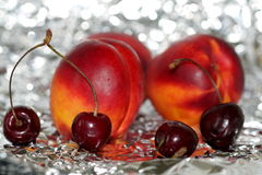 Fruits in tin-foil. Two nectarines and four red cherries lie ornamentally on a crumpled tin-foil stretched out stock photos