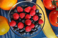 Fruits and tomato mix. Inside bowl and around Royalty Free Stock Photos