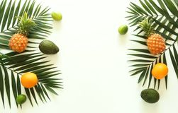 Fruits top view background. tropical green palm leaves branches and fruits pineapples stock photos