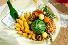 Fruits tropicaux frais sur la plage au panier Fruits tropicaux assortis, bananes, ananas contre l'ananas, pastèque Images libres de droits