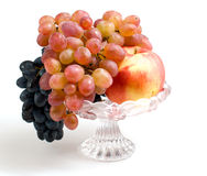 Fruits in a vase. Yellow apple, dark and bright grapes in a vase on a white background Stock Photo