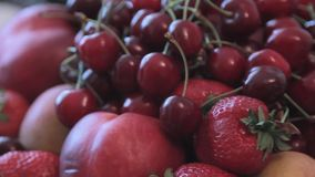 Fruits in a vase. Cherries, strawberries, apples are in the vase. Hitting the camera. In a vase are the fruits for the holiday table. Close-up stock footage