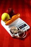 Fruits and Vegetable on a Weighing Scale with a Measuring Tape Royalty Free Stock Photos