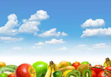 Fruits and vegetables. Collage from fruits and vegetables against blue summer cloudy sky Stock Photo