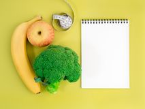 Fruits and vegetables - apple, banana and broccoli on bright yellow background. Notebook to record about diet. royalty free stock photography