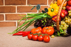 Fruits and vegetables arranged in a group. Fruits and vegetables like tomatoes, zucchini, tomatoes, pepper and grapes arranged in a group into wicker basket Stock Photos