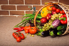 Fruits and vegetables arranged in a group. Fruits and vegetables like tomatoes, zucchini, tomatoes, pepper and grapes arranged in a group into wicker basket Stock Photography