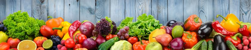 Fruits and vegetables on background of wooden wall. Healthy vege Royalty Free Stock Photo