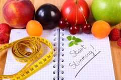 Fruits, vegetables and centimeter with notebook, slimming and healthy food Stock Image