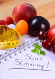 Fruits, vegetables and centimeter with notebook, slimming and healthy food Royalty Free Stock Photo