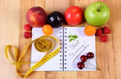 Fruits, vegetables and centimeter with notebook, slimming and healthy food Royalty Free Stock Photos