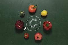 Fruits and vegetables contain vitamin c. Fruits and vegetables laying on green chalkboard contain vitamin c Royalty Free Stock Images