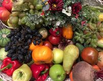 Fruits and vegetables. Different fruits and vegetables are laing in tbe basket decorated with autumn flowers. Photo may be able to use for Thanksgiving card or Stock Photography
