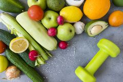 Fruits and vegetables , dumbbell on a gray background, apples, zucchini, cucumbers, avocado, radish, garlic, tomato, lemon, orange. Fruits and vegetables stock photos