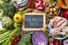 Fruits, vegetables, fish, meat, text balanced diet. A chalkboard with the text balanced diet written in it, on a table full of a different raw fruits and royalty free stock photography