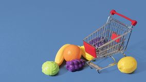 Fruits and vegetables on the floor around an empty shopping cart. Empty shopping cart trolley surrounded by giant toy fruits and vegetables on the floor on a Stock Image