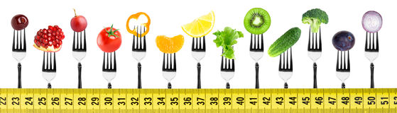 Fruits and vegetables on fork with measuring tape Royalty Free Stock Photography