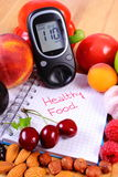 Fruits and vegetables with glucometer and notebook for notes, healthy food, diabetes. Fresh fruits, vegetables and glucose meter on notebook for writing notes Royalty Free Stock Photography