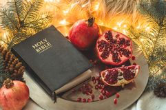Fruits and vegetables for harvesting. Still life - bible and pomegranate on an iron plate in the branches of the Christmas tree stock image