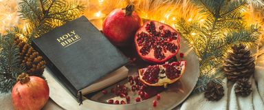Fruits and vegetables for harvesting. Still life - bible and pomegranate on an iron plate in the branches of the Christmas tree. royalty free stock photography