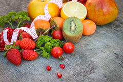 Fruits, vegetables and in measure tape in diet on wooden background Stock Photo
