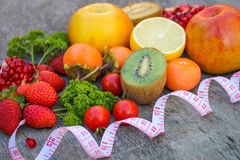 Fruits, vegetables and in measure tape in diet on wooden background Stock Image