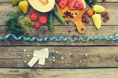 Fruits, vegetables, measure tape, pills on wooden background. Concept of different ways to lose weight. royalty free stock photos