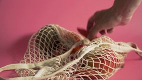 Fruits and vegetables in mesh bag, alternative to plastic shopping bags on pink background 4k. Fruits and vegetables in mesh bag, alternative to plastic shopping stock footage