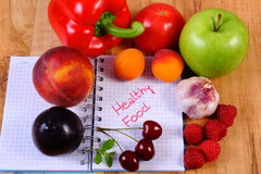 Fruits and vegetables with notebook, slimming and healthy food Stock Images