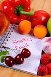 Fruits and vegetables with notebook, slimming and healthy food Stock Image