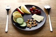 Fruits, vegetables, nuts and crackers on a plate Royalty Free Stock Photography